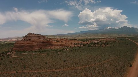Aerial drone flight over desert scrubland and red rocks at sunset in Utah.