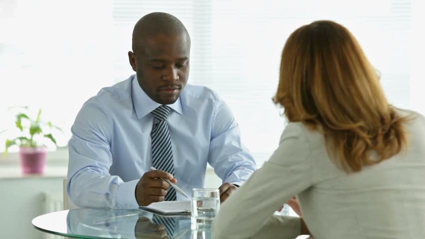 Young African-American man looking through the contract and asking his partner to clarify some clauses #2151095
