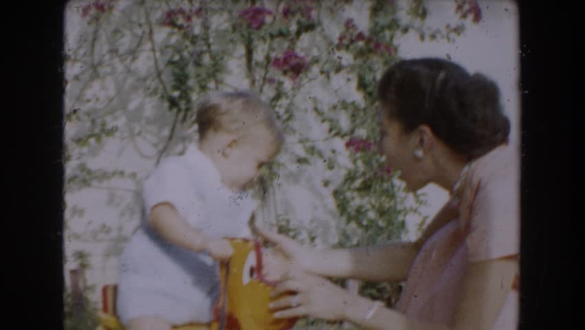 GLENDALE, CALIFORNIA 1962: a mom playing and helping her young son to take his first steps
