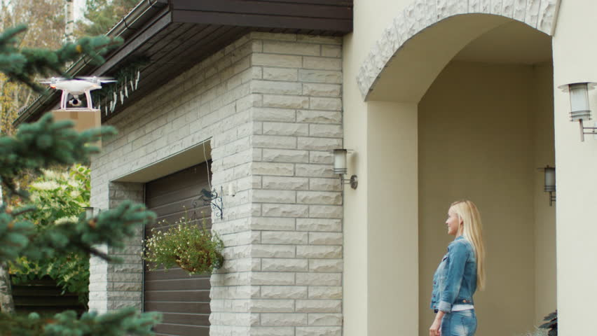 Smiling Woman Stands on a Porch While Flying Drone Delivers Her Postal Package to Her. Contactless Delivery Concept People Receiving Medical Aid, Essentials and Food Delivery in the Safety of Home