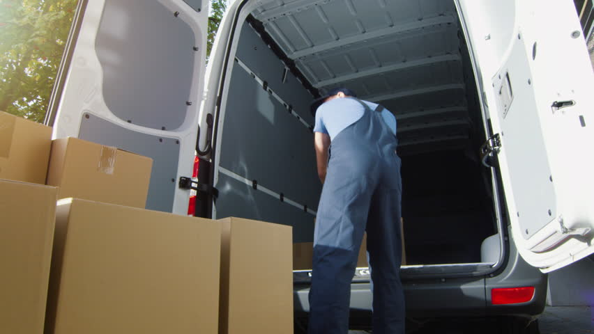 Delivery Man Loads Cardboard Boxes into his Van. Slow Motion. Shot on RED Cinema Camera in 4K (UHD). Royalty-Free Stock Footage #21531481
