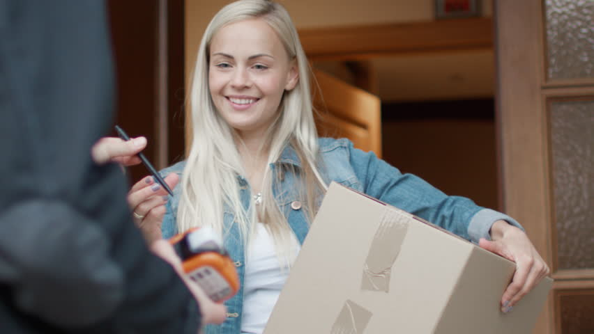 Smiling Woman Receives Postal Package after Signing Electronic Signature Device while Standing in the Open Doorway. Shot on RED Cinema Camera in 4K (UHD). #21531508