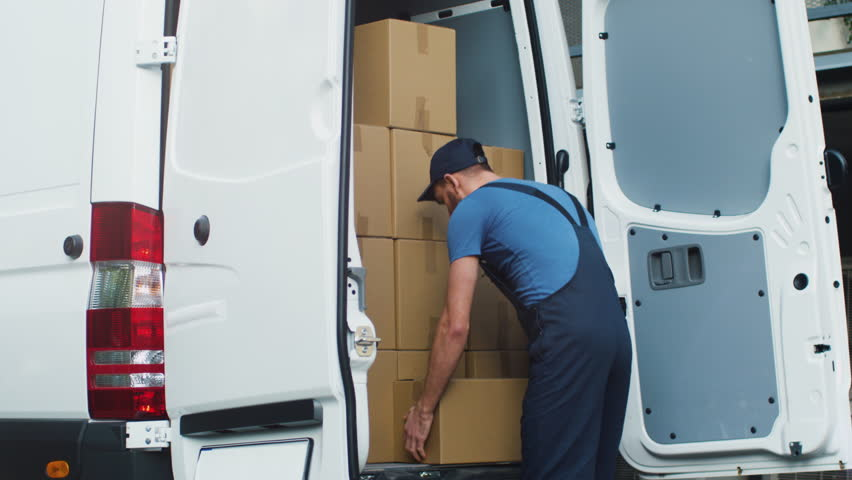 Young and Smiling Delivery Service Man Takes Cardboard Box from his Cargo Van and Walks towards Delivery Destination. Shot on RED Cinema Camera in 4K (UHD). Royalty-Free Stock Footage #21531523