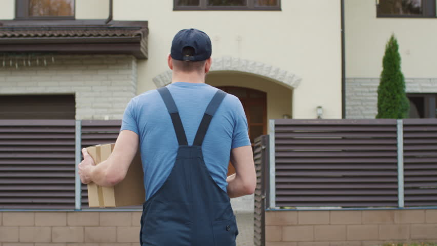 Delivery Man Comes To the Suburban House Door and Knocks. Camera Follows Him from the Back. Shot on RED Cinema Camera in 4K (UHD). Royalty-Free Stock Footage #21531565