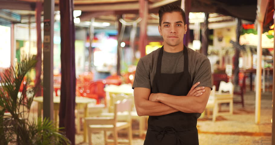 Happy handsome young Latino waiter standing in outdoor patio of restaurant smiling. Friendly millennial server wearing apron while waiting tables at small business. 4k