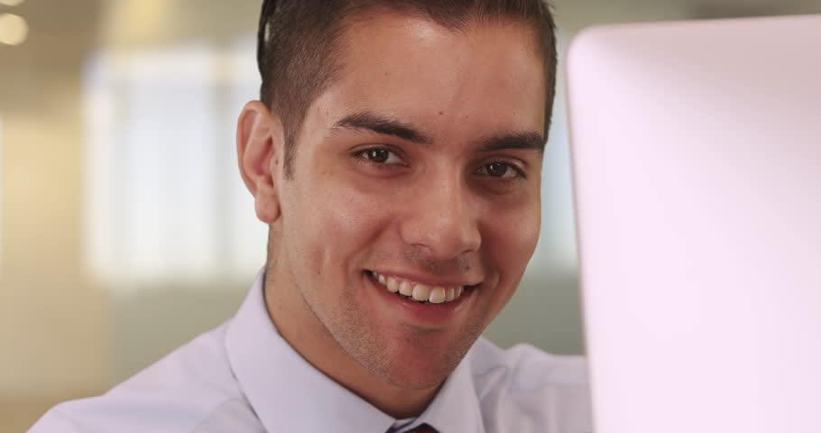 Portrait of handsome Latino business man sitting at computer smiling. Attractive happy young Hispanic professional in office looking at camera. 4k | Shutterstock HD Video #21542191