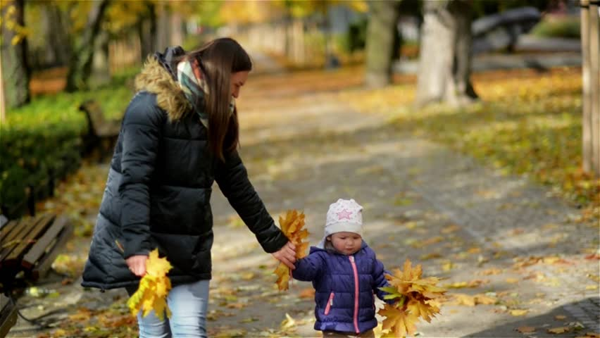 Mother and Daughter Walking Holding Hands at Park. They are Wearing Warm Clothes, Autumn Season. | Shutterstock HD Video #21544633