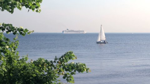 Yacht cruising On A Bay Of The Baltic Sea in summer day. White Yacht at inflated sails Floating In The calm blue water. On The Far Can Be Seen The big cruise liner,Saint Petersburg, Russia, june 2016