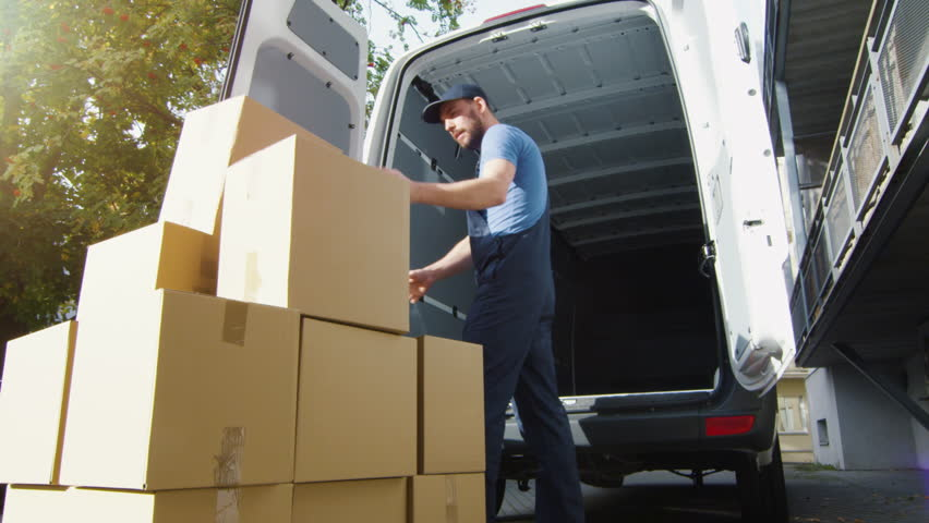 Delivery Man Loads Cardboard Boxes into his Van. Slow Motion. Shot on RED Cinema Camera in 4K (UHD) #21556186