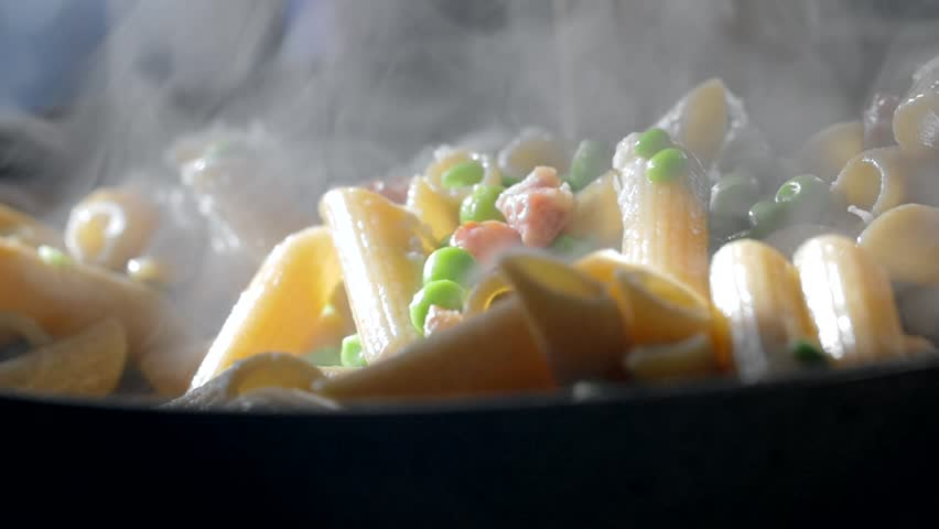 A woman is cooking penne pasta in a skillet dressed with green beans and diced bacon. Closeup slow motion shot. #21559600