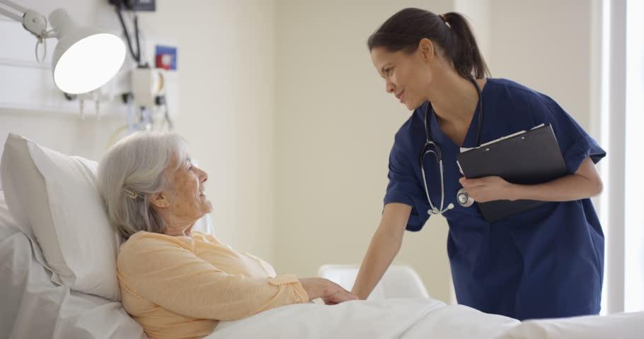 4K Caring medical worker in hospital talking to elderly lady at her bedside (UK-Oct 2016)