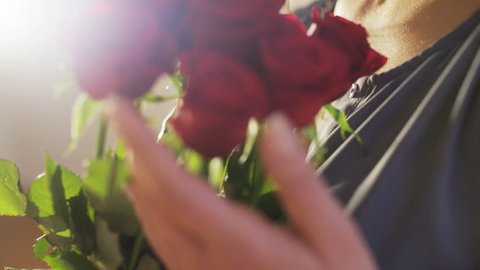 Woman Holds a Bouquet of Red Roses