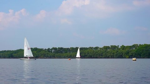 a team of the sailboats floating on a lake with a blue sky background.