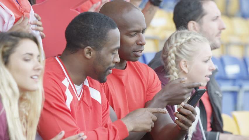 4K Spectators watching sports game in stadium, 2 men looking at smartphone (UK-Oct 2016)   Shutterstock HD Video #21604396