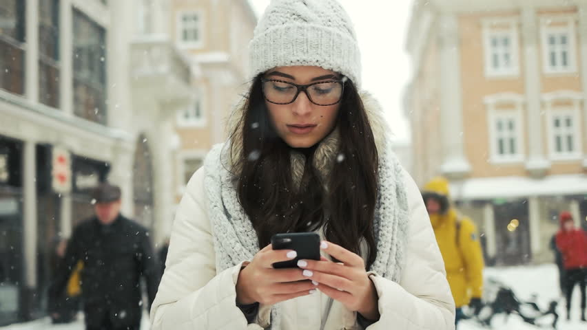 Beautifulwoman wearing winter coat and smiling happy while sending message with cellphone in the city