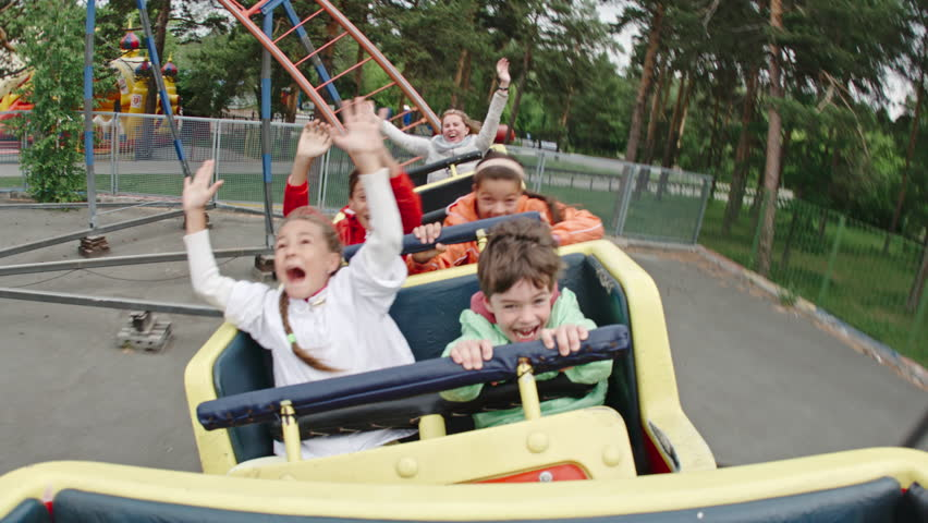 Joyful kids screaming and raising arms while riding roller coaster in amusement park