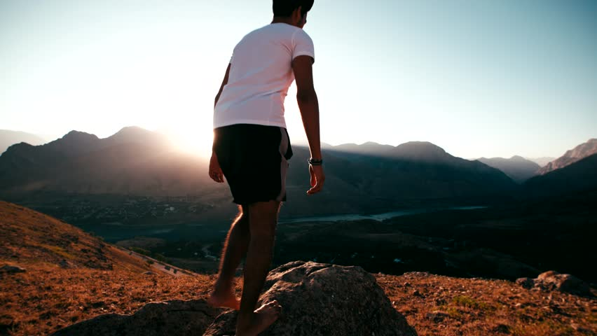 young Asian male reaching to the top of the mountain area, standing on top of the mountain, raised hands, slow motion #21664531