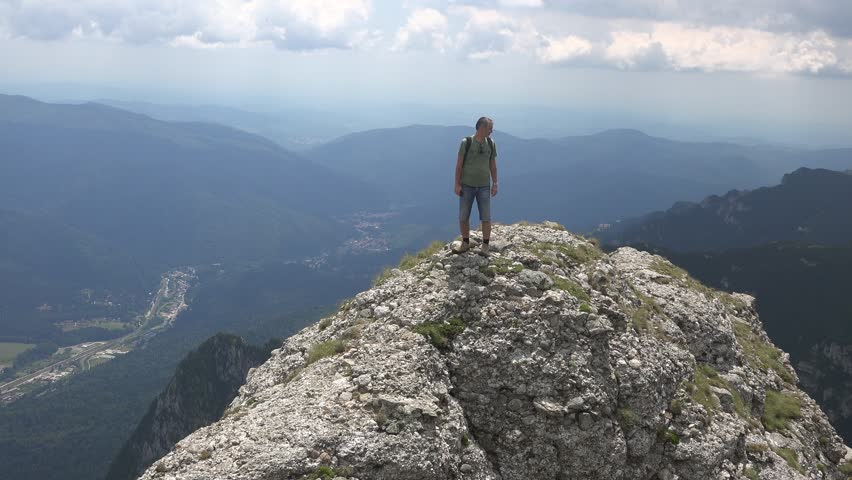 CARAIMAN MOUNTAINS, ROMANIA - Circa JULY 2016:Man on top of a cliff taking pictures.View of Busteni town, Romania, near to Heroes Cross , Caraiman Mountains, Romania, 4k, UHD | Shutterstock HD Video #21669829