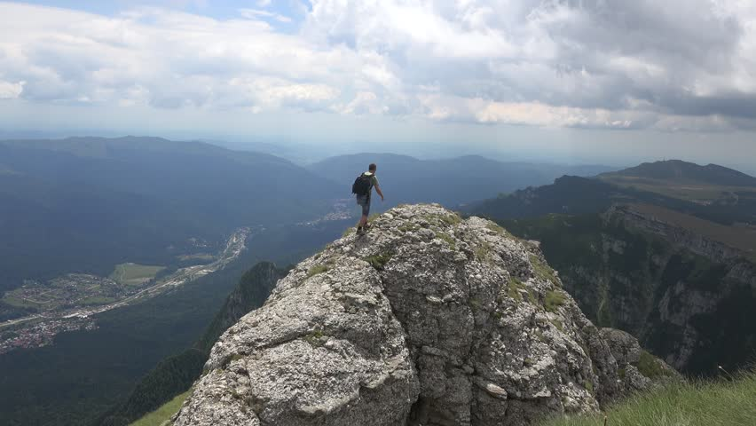 CARAIMAN MOUNTAINS, ROMANIA - Circa JULY 2016:Man climbing on top of a cliff and makes a gesture with hands.View of Busteni town, Romania, near to Heroes Cross , Caraiman Mountains, Romania, 4k, UHD | Shutterstock HD Video #21669847