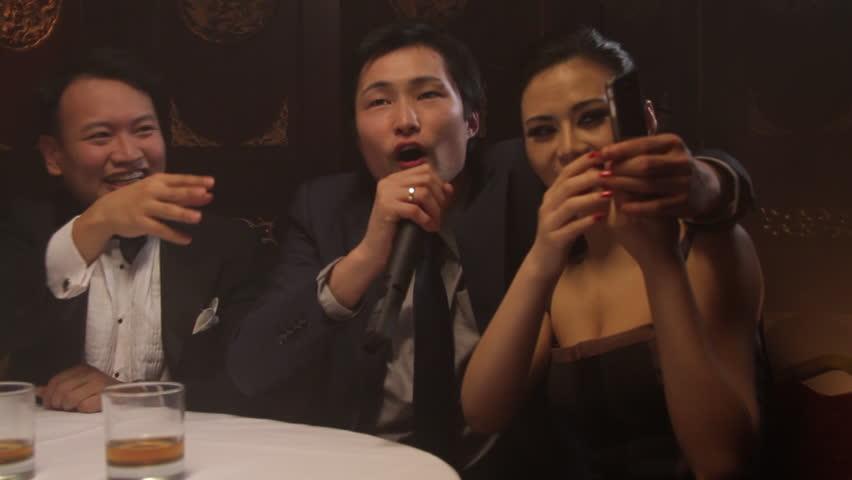 Male singing karaoke in Chinese restaurant, female taking picture | Shutterstock HD Video #2168201