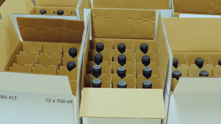 Packaging bottle with alcohol. Work puts bottle of wine in cardboard boxes Royalty-Free Stock Footage #21683683