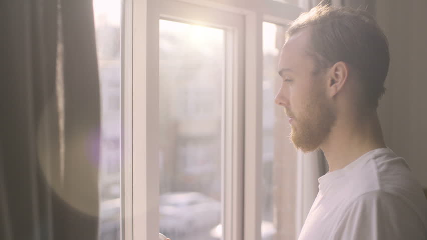 Young male opens curtains to bright sunny day, sips coffee and looks out of window, filmed at half speed. Royalty-Free Stock Footage #21685936