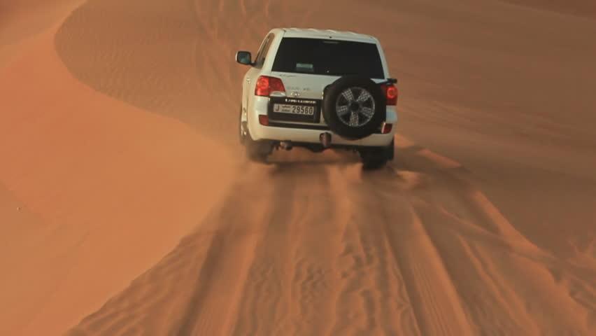 ABU DHABI, UAE - AUGUST 20, 2014: Desert Safari SUVs bashing through the arabian sand dunes. View from the car 13.