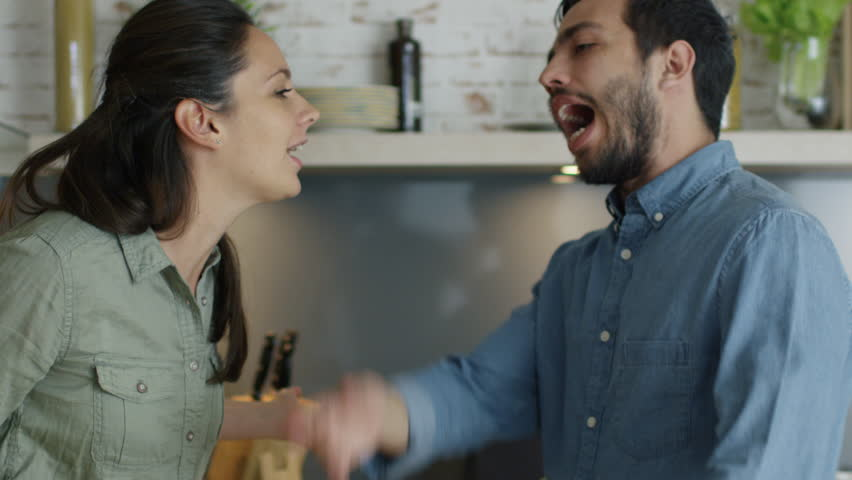 Young Couple Quarrels in the Kitchen. Man and Woman Scream in Frustration and Angrily Gesticulate. Shot on RED Cinema Camera in 4K (UHD).