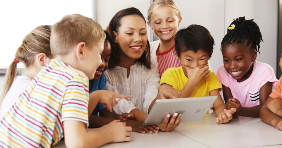 Front view of Caucasian female teacher teaching school kids on digital tablet in classroom at school #21730702