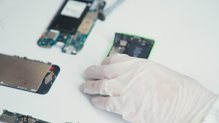 Close-up of a cell phone repair. The internal components of a smartphone. Disassembled cell phone. Cell Phone Battery. Master disassembled mobile device for detail. Chips and details of the smartphone Royalty-Free Stock Footage #21738004