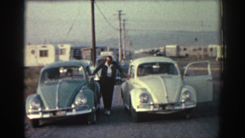 RHODES GREECE 1962: man poses with two vw beetles