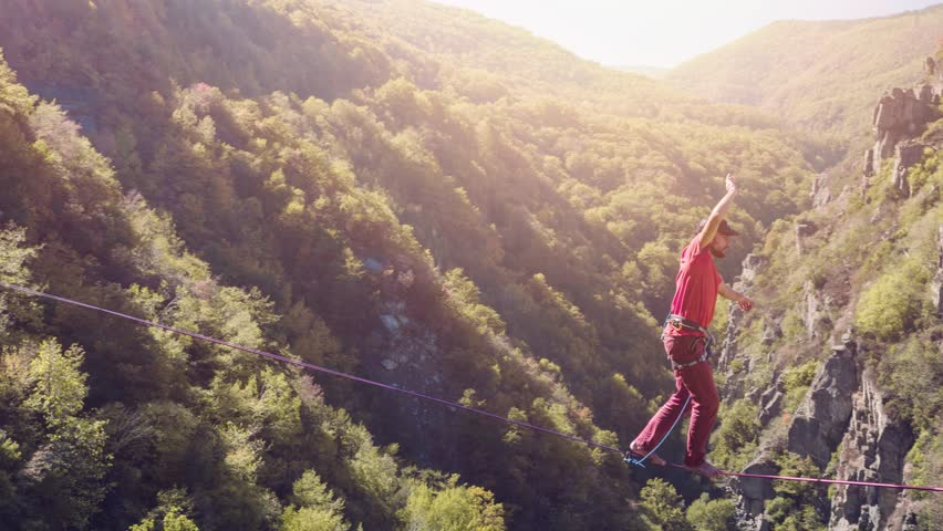 Brave Young Man Balancing On Rope Above Mountains Tree Nature Adventure Slacklining Sport Danger Hiker Walking Extreme Sunny Leisure Performance Fear | Shutterstock HD Video #21762754