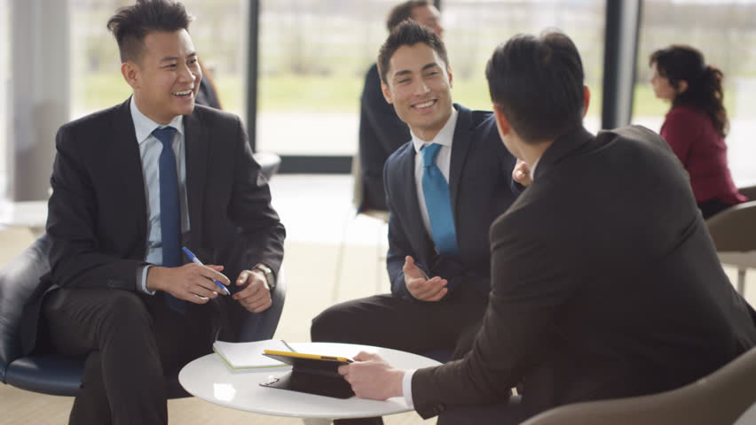 4K Asian businessmen in discussion in busy meeting area of modern office (UK-Oct 2016)