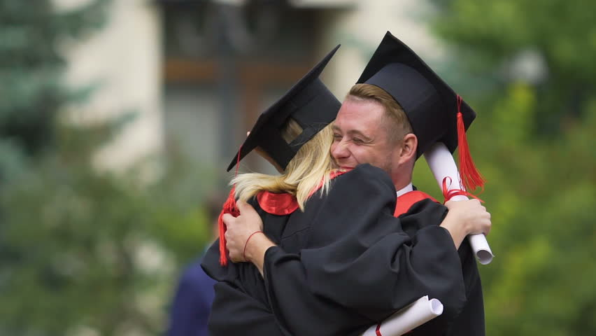 Best friends hugging warmly and laughing, celebrating graduation from university