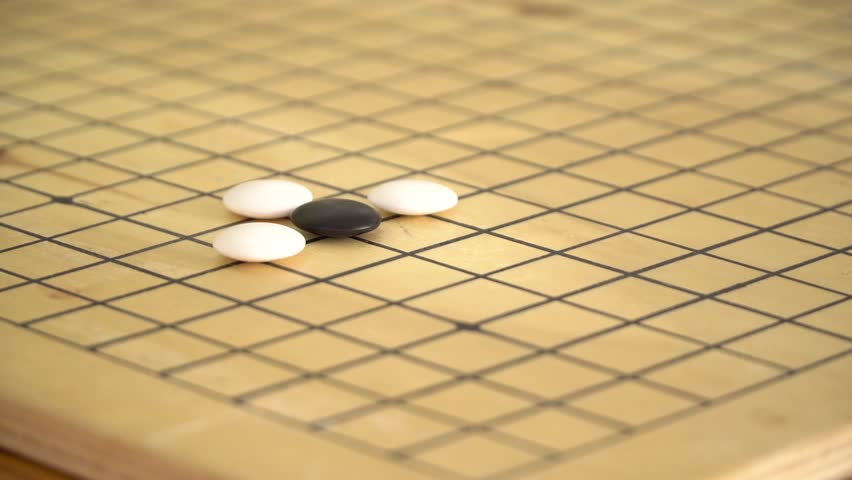 Chinese go game weiqi playing atari position on wooden board