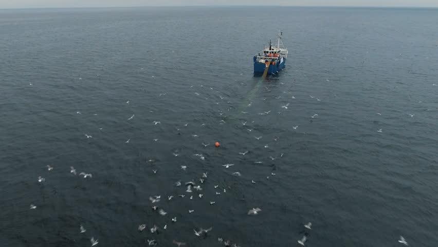 Flying towards a Commercial Fishing Ship that Pulls Trawl Net. Shot on Phantom 4K UHD Camera.