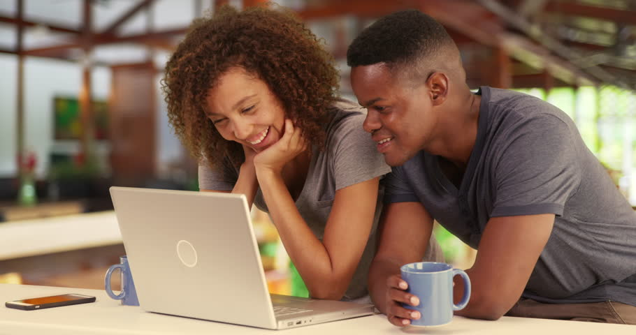 Black millennial couple working together or watching video on laptop in cafe. African American man and woman in restaurant or coffee shop drinking coffee and using computer. 4k | Shutterstock HD Video #21848911