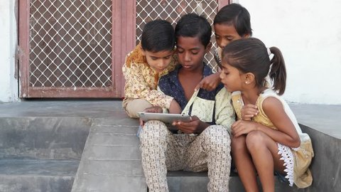 Kids busy on a touchscreen tablet, elder sibling teaching them, close up handheld