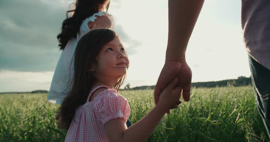 little Asian girl walking on the green field with their parents, holding the hand of his father, slow motion #21874597