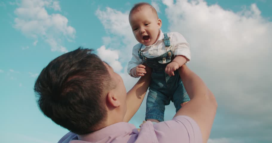 portrait of happy Asian father holds his son for 1 year, playing with the baby, slow motion