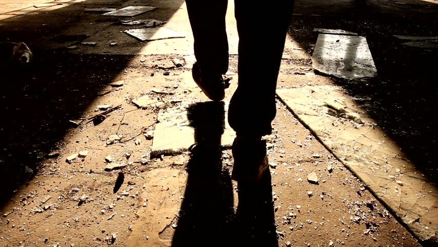 Murderer walks away, leaving the crime scene in some old ,dark,messy building. Shadows are visible, high contrast made of sunlight falling through opened door.