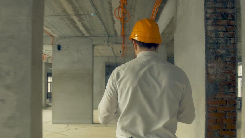 Investor inspecting building. Businessman in hard hat inside construction site examining construction progress.