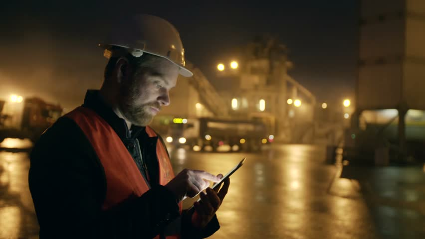 Engineer in hardhat with a tablet computer looks at truck on heavy industry
