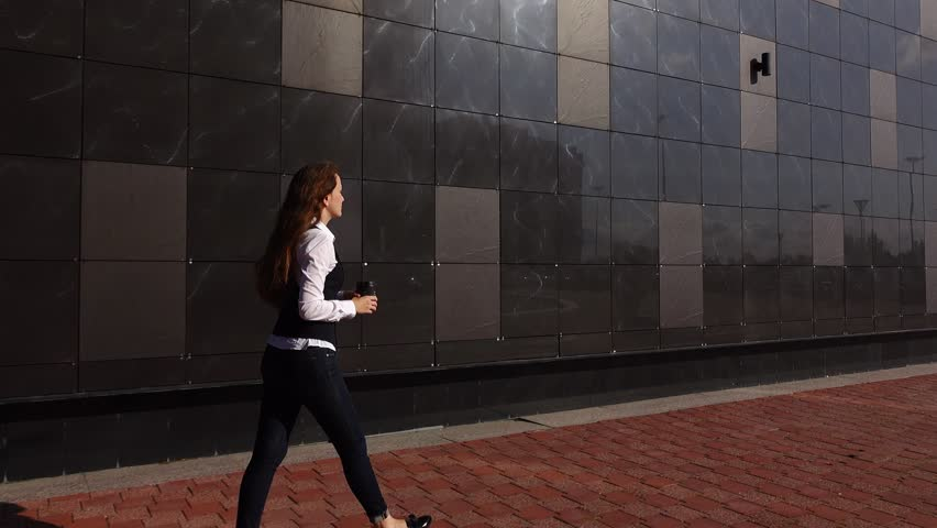 Young adult office woman walk away along glossy building wall. Full length shot of white collar worker in formal attire. She have lunch break and come out for cup of coffee. Glide camera follow beside | Shutterstock HD Video #21915094