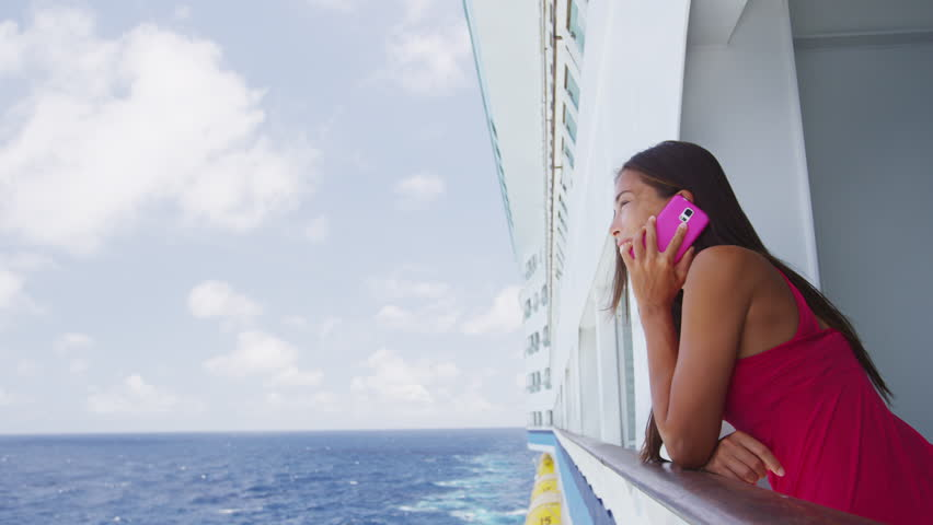 Smartphone woman texting, calling and talking having phone conversation on cruise ship travel vacation with ocean in background standing on balcony. Girl using smart phone on holiday.