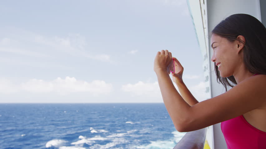 Passenger on cruise ship vacation taking photo with phone camera enjoying travel at sea. Girl using smartphone to take picture. Woman in dress on luxury cruise liner boat.