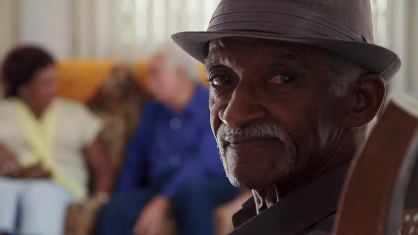 Portrait of elderly black man looking at camera. Group of friends in retirement home. Old people in medical clinic. Patients relaxing in hospice for seniors. Slow motion
