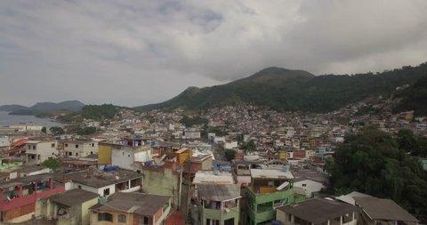 Favela Aerial: backwards reveal of hilltop favela on the edge of a coastal town