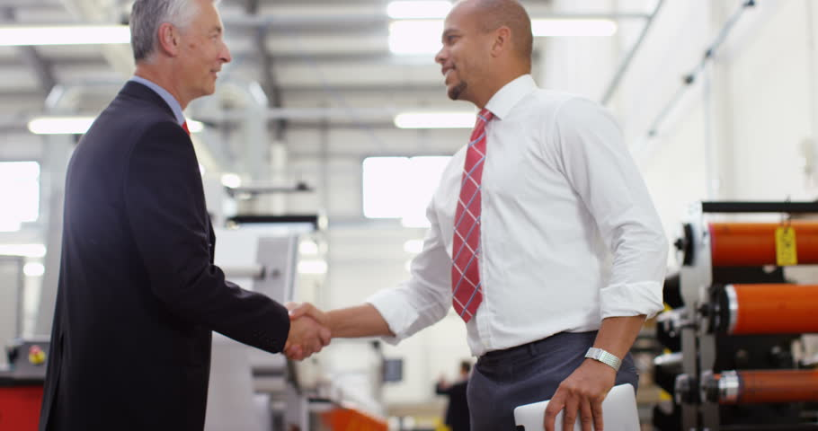4K Businessmen greet each other & shake hands on the factory floor, looking at computer tablet & discussing operations Royalty-Free Stock Footage #21974833