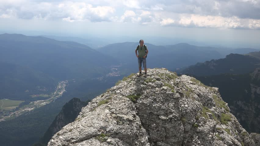 CARAIMAN MOUNTAINS, ROMANIA - Circa JULY 2016:Man on top of a cliff taking pictures.View of Busteni town, Romania, near to Heroes Cross , Caraiman Mountains, Romania, 4k, UHD | Shutterstock HD Video #21982120